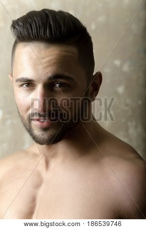 model with muscular chest bearded young man or athlete with wrinkle forehead stylish beard and hair haircut posing on beige concrete wall. Male beauty and sport