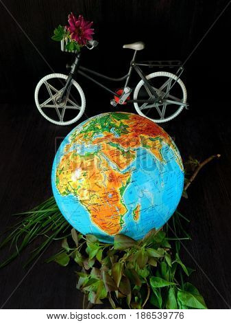 Globe and a bicycle on a black background. Travel concept. Environment concept
