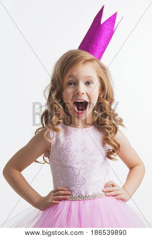 Little princess girl in pink crown and beautiful dress on white background