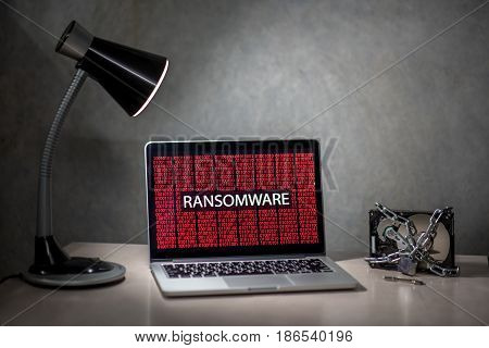 Computer screen with ransomware attack alert in red digital binary background with hard disk drive lock. Cyber attack concept