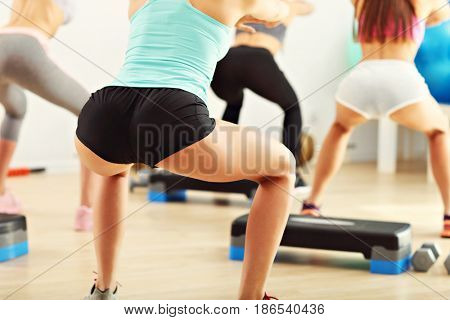 Group of women working out in gym doing squats