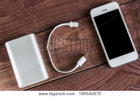 Grey Portable External Battery ( Powerbank ) With Usb Cable And Phone On Wooden Background