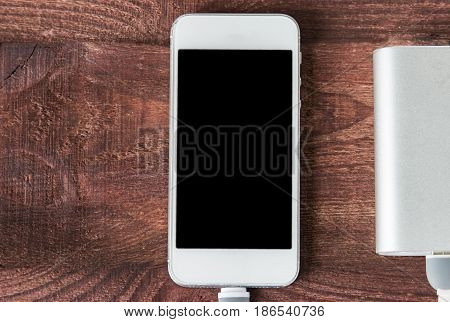 Grey Portable External Battery ( Powerbank ) With Usb Cable And Phone On Wooden Table