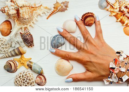 Girls hand with manicure on the white wooden table with sea shells between fingers