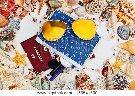 Blue cosmetic bag with anchor print sunglasses and passport on the table with a frame of sea shells and starfish - horizontal top view