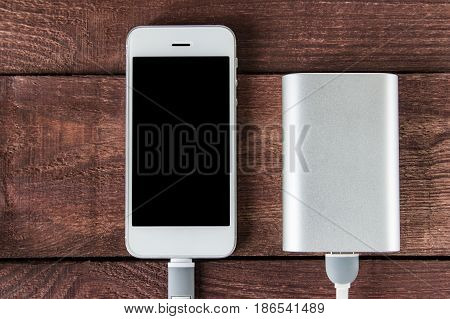 Charging Smartphone With Powerbank On A Wooden Desk . Portable External Battery