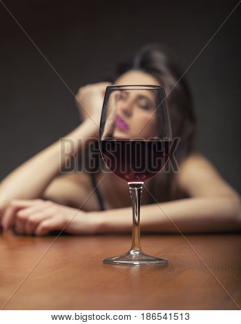 Woman in depression drinking alcohol on dark background. Focus on the glass