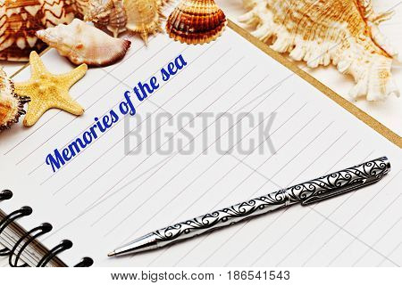 Close up shooted blank lined diary with an inked tagline and sea shells
