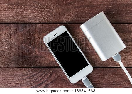 Grey Phone And Power Bank Connected By Cord On Wooden Planks