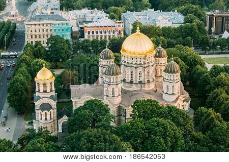 Riga, Latvia. Riga Cityscape. Top View Of Riga Nativity Of Christ Cathedral - Famous Church And Landmark In Summer Evening. Golden Yellow Domes.