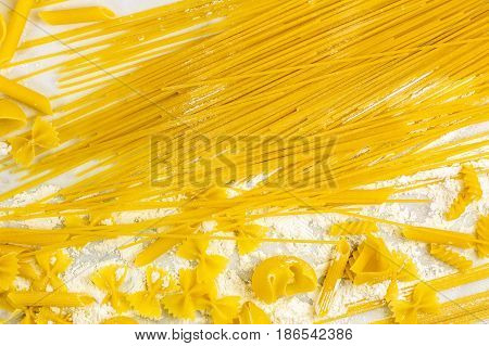 Vibrant pasta texture with spaghetti, penne, bowtie pasta, shells and spirals, on a white marble table with flour