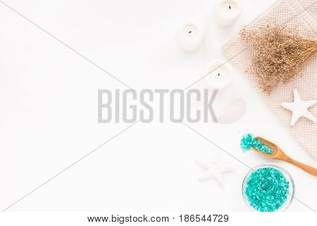 Spa composition with candles sea salt and flowers on white wooden background. Flat lay.