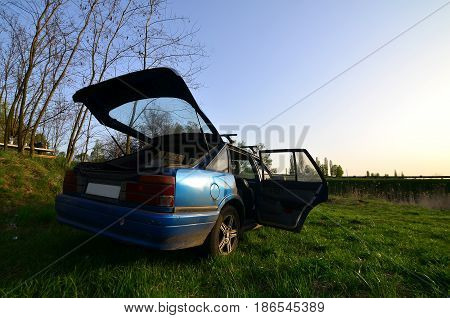 A Blue Car On A Background Of A Rustic Landscape With A Wild Cane Field And A Small Lake. The Family