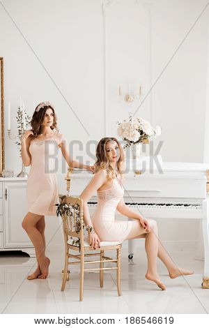 Couple of two beautiful girls in pink nightie dress with elements of lace siting against white piano and posing. Girlfriends with wavy hair posing in luxury interior. Morning look.