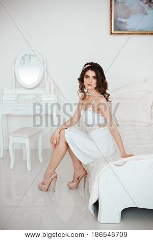 Sensuality beautiful woman in white lace nightie dress and beige heels, accessories in hair and necklace, sitting and posing on bed. Luxury interior of white bedroom. Morning bride look.