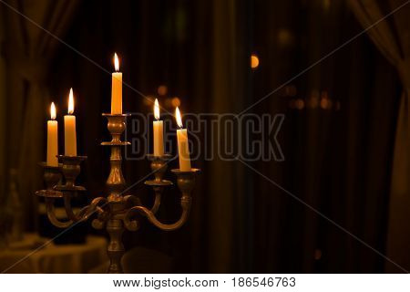 Metal retro candlestick with five burning candles against a dark background in the room home selective focus. Horizontal Image for design with place for your text