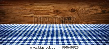 Blue checkered tablecloth in front of a rustic wooden wall for a bavarian concept