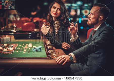 Upper class couple gambling in a casino