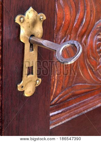 Ancient metal key against the background of antique furniture