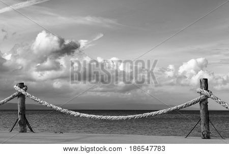 Black and white view on seafront and sky with sunlight clouds in autumn evening. Turkey Erdek coast of Marmara.