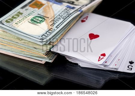 four poker aces with dollar isolated on black.