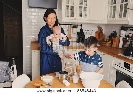happy family baking together in modern white kitchen. Mother son and baby daughter cooking in cozy weekend morning at home