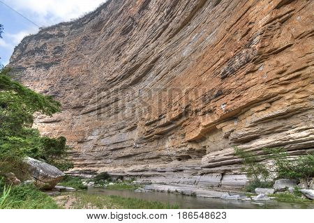 Huge vertical wall with river below at Tapesco del Diablo cave in Rio la Venta Canyon in Chiapas Mexico