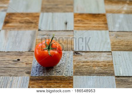 Wooden table from different wood mosaik textures, as chess board and fresh organic ripe tomato with water drops. Healthy eating concept, antioxidant and diet