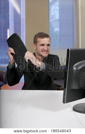 Angry man using a desktop computer for business