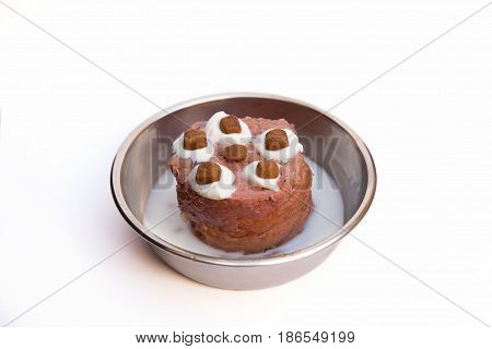 birthday cake for a cat with whipped cream and goodies in a bowl with milk
