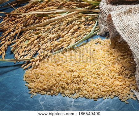 Brown rice uncooked in a bag with a pile of brown rice and spike rice on table background.