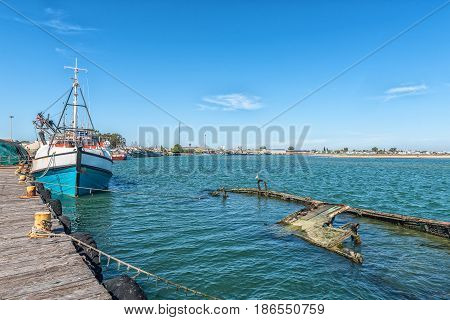 LAAIPLEK SOUTH AFRICA - APRIL 1 2017: Fishing ships and a sunken boat in the harbor at the mouth of the Berg River at Laaiplek on the Atlantic coast of South Africa