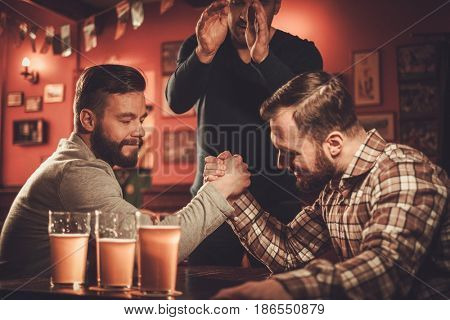 Cheerful old friends having arm wrestling challenge in a pub.