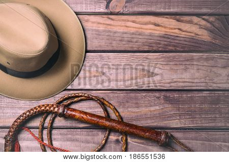 Travel and adventure concept. Vintage fedora hat and bullwhip on wooden table. Top view.