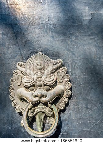 Bronze lion head door knocker in traditional Chinese design style. Weathered cracks in wooden backing.