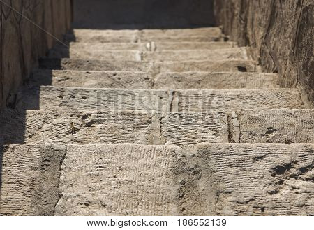 Closeup detail of stone paved steps on rural footpath walkway going downwards to blurred background
