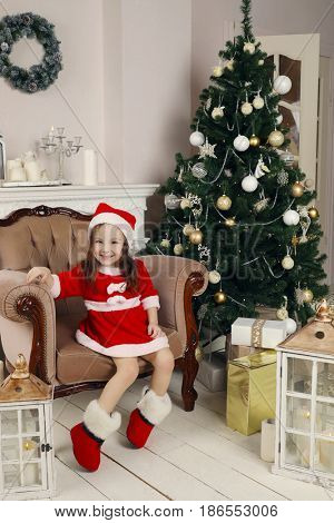 Little girl in santa costume and felt boot poses in armchair in room with christmas tree
