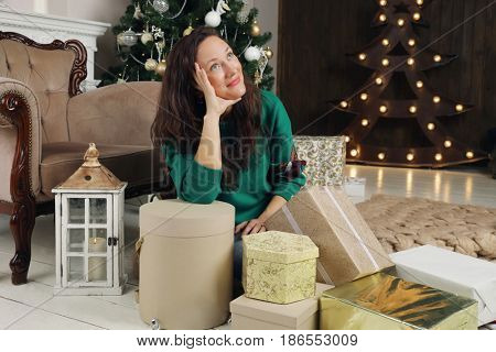 Young woman in green sits on floor among many gifts in room with christmas tree and illumination