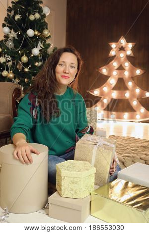 Happy woman in green sits on floor among many gifts in room with christmas tree and illumination
