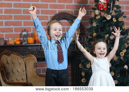 Boy and girl have fun with raised arms near christmas tree with dried oranges in brick studio, focus on boy