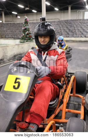 Man in helmet prepares for driving competition of karting, child behind him out of focus