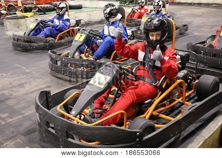Five adults and one child in helmets prepares for driving karting, Woman in red thumbs up, focus on right woman