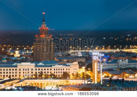 Riga, Latvia - July 2, 2016: Aerial View Of Cityscape In Summer Evening Or Night Lights Illumination. Top View Of Building Of Latvian Academy Of Sciences At Blue Hour
