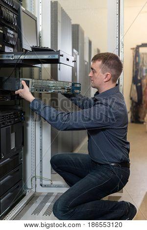 IT Engineer installs equipment in the rack in datacenter