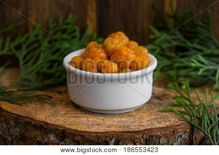Pickled Cloudberries in a sweet syrup in a white bowl on the wooden background with the leaves of juniper.