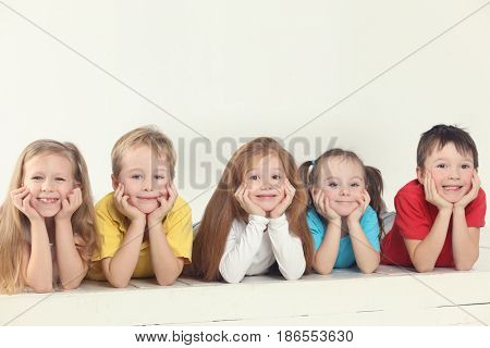 Five happy children (three girls and two boys) pose in white studio