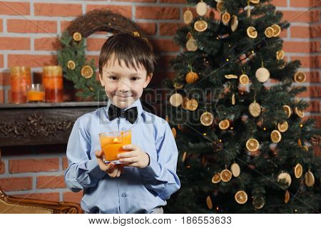 Little boy with bow tie holds burning candle near christmas tree in brick studio