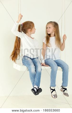 Two happy little girls in jeans swings and look at each other in white studio