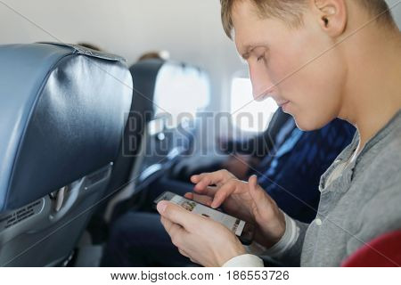 Man with cell phone is in flying aircraft, shallow dof, profile