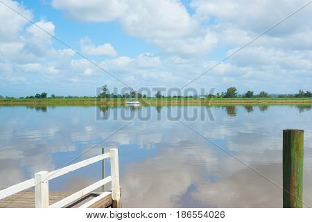Green of sugar cane plantation across Clarence River with clouds reflected in calm water from jetty with yacht moored on other side near Australian town of Ulmara